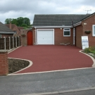 pigmented red driveway with natural border